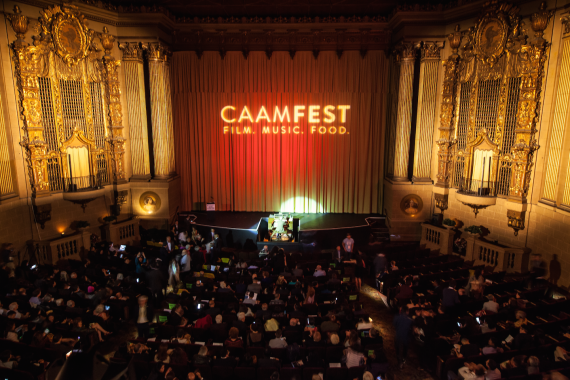"A darkened Castro Theater in San Francisco with the words ""CAAMFEST: FILM, MUSIC, FOOD"" projected onto the red curtain."