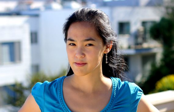A young Chinese American woman wearing a bright blue shirt is standing in the sun and looking at the camera. Playwright Lauren Yee.