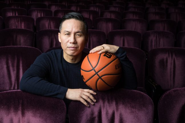 A middle aged Chinese American actor sits among an empty theater with velvet seats. He is looking at the camera and holding an orange basketball. The actor is BD Wong.