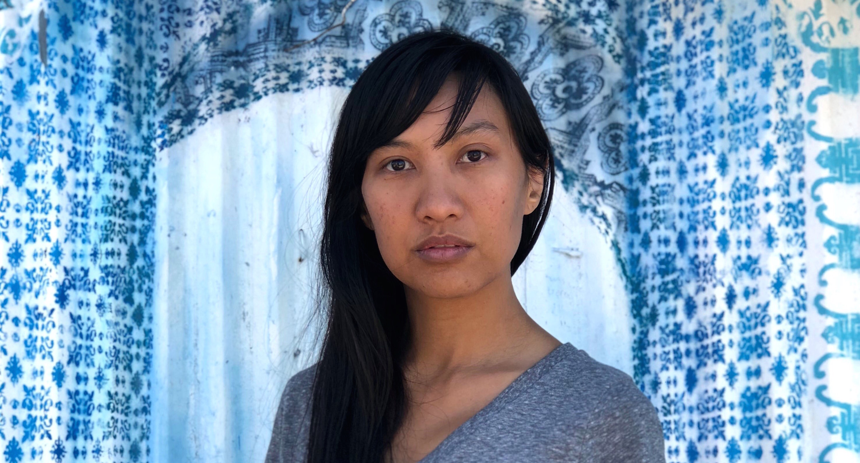 A Filipina American woman with long black hair and bangs looks into the camera for her portrait.
