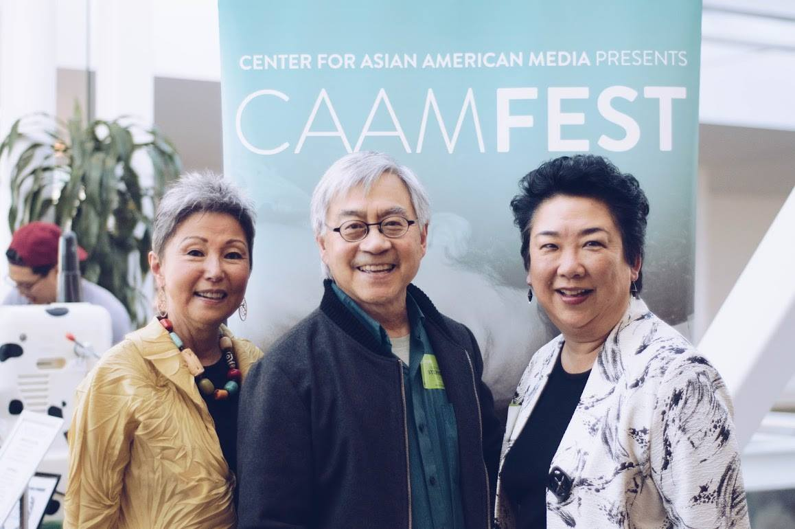 Three people at the CAAMFest 2018 Preview Screening standing in front of a CAAMFest banner and smiling.