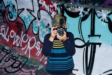 A young Asian American woman with short blondish hair is holding a camera in front of her face; there is a graffiti'ed wall in the background.