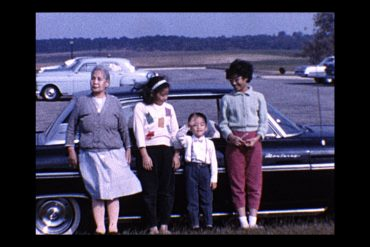 An image of an Asian American family that is a still from a family home movie.