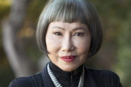 A Chinese American woman with silver grey hair and red lipstick looks at the camera for her headshot. The person is author Amy Tan.