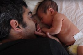 A South Asian man is on the bed facing his newborn son.