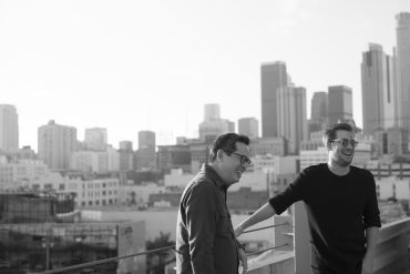 An Asian American man with short hair and glasses is laughing with a Caucasian man, with the cityscape behind them.