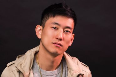 A Korean American Jake Choi looks at the camera for his headshot.