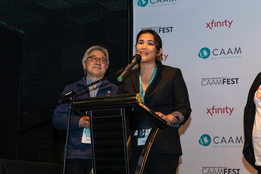 "CAAM Executive Director Stephen Gongs gives the Comcast Narrative Award winner Diane Paragas her award for ""Yellow Rose"" at the CAAM Filmmaker Awards Brunch. Photo by Kelsey Ogden."