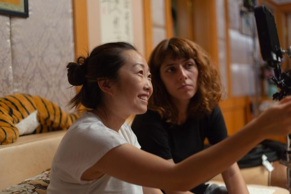 "An Asian American film director, Lulu Wang, has her hair in a ponytail bun and smiles while she's pointing. She is the director of ""The Farewell."""