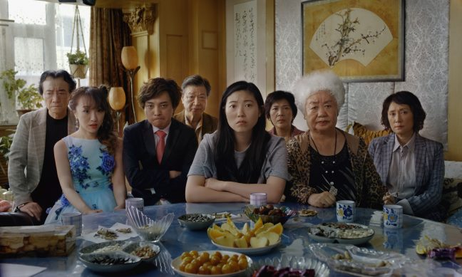 A group of Asian Americans sit at a table looking at the camera with no smiles.