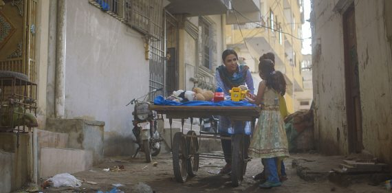 A transgender woman on the streets of Karachi, Pakistan, stands and chats with a young child while pushing a cart of stuffed animals
