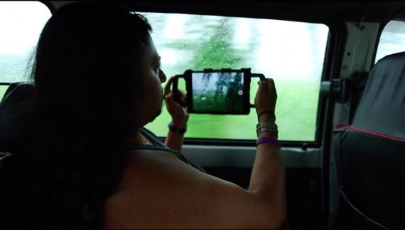 An image of a South Asian man with long hair sitting in a car and filming the greenery outside on his phone.