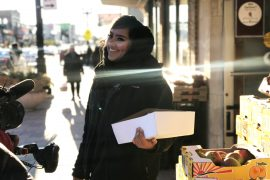 A woman wearing a hijab looks into the distance while holding a box of produce.