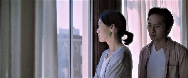 A Korean American woman stares forlornly out the window while her son, a young man, looks at her.