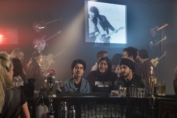 Three Pakistani British sit at a bar with an image of Bruce Springsteen in the background.