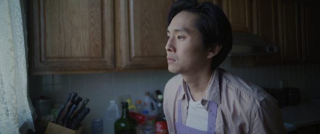A Korean American man looks off into the distance forlornly.