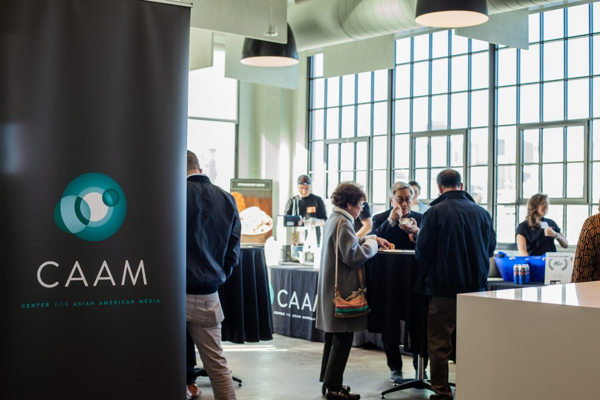 "A banner that says ""CAAM"" with a dark grey background. People in the background are mingling in a hip, well-lit space."