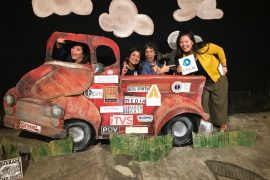 Four people pose joyfully behind an old car in a photo booth. The old car is covered with stickers from nonprofit media arts organizations, including CAAM.