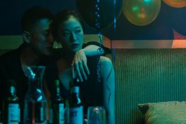 A woman looks off into the distance in a moody bar, while an Asian American man turns toward her face.