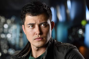 A mixed race Asian American man looks intensely into the distance.