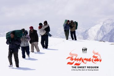 An image of people trekking through the snow filled Himalayan mountains.
