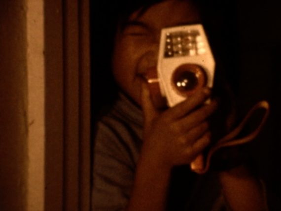 A screenshot of a young Asian American child holding an old video recording device.