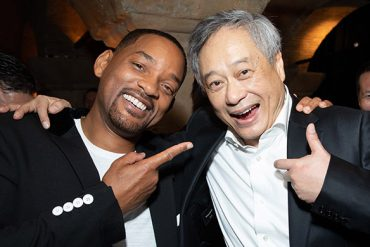 An African American man and Chinese American man smile for the camera while they are hugging.