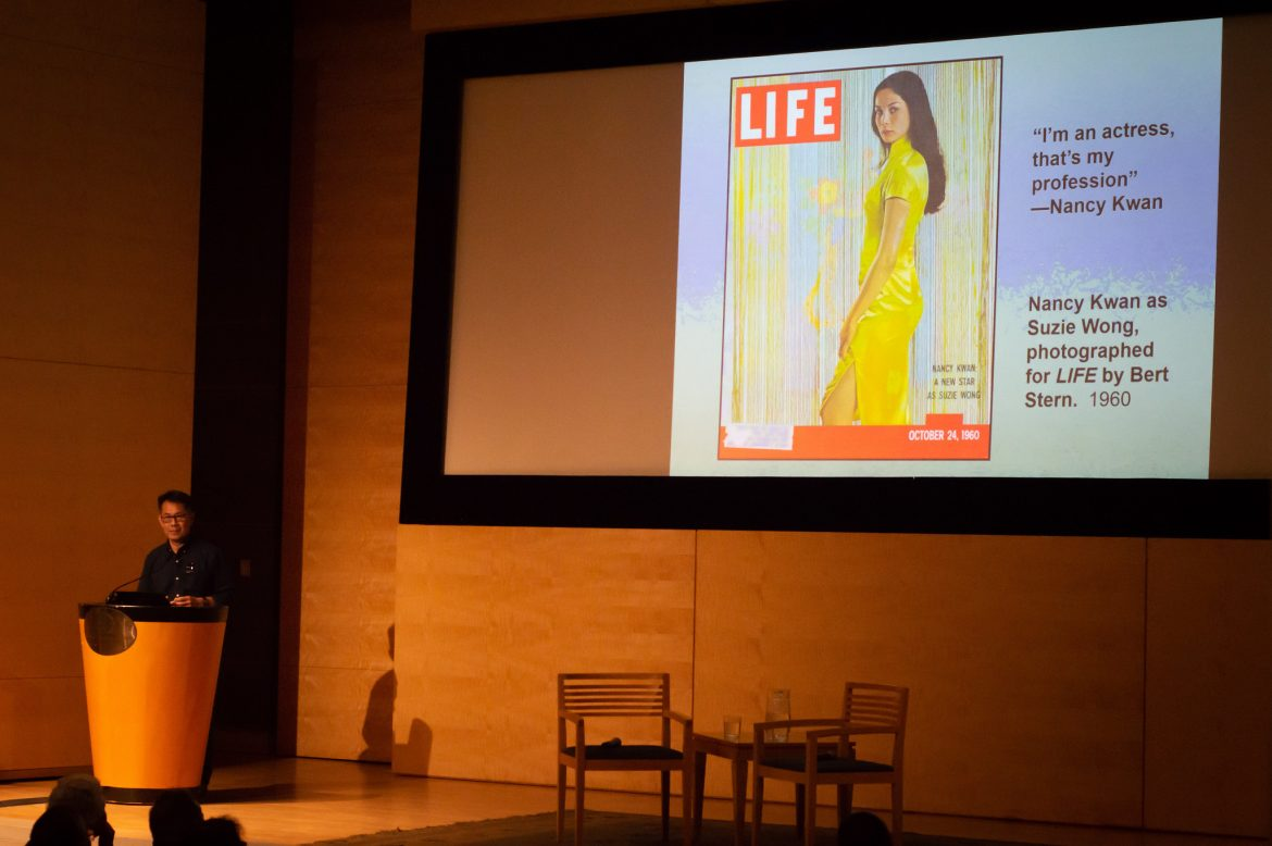An older Chinese American man stands at the podium with an image of Nancy Kwan on the cover of LIFE magazine projected on a screen.