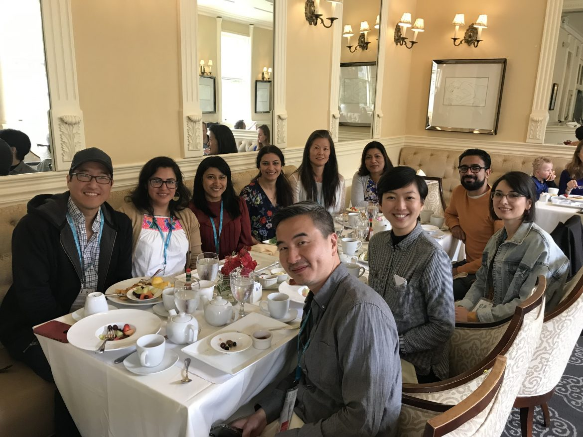 A group of mixed Asian Americans sit at a well lit dining table and smile at the camera.