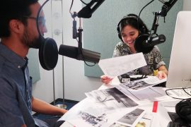 Two Asian Americans, a man and a woman, sit at a table in an audio studio during an interview.