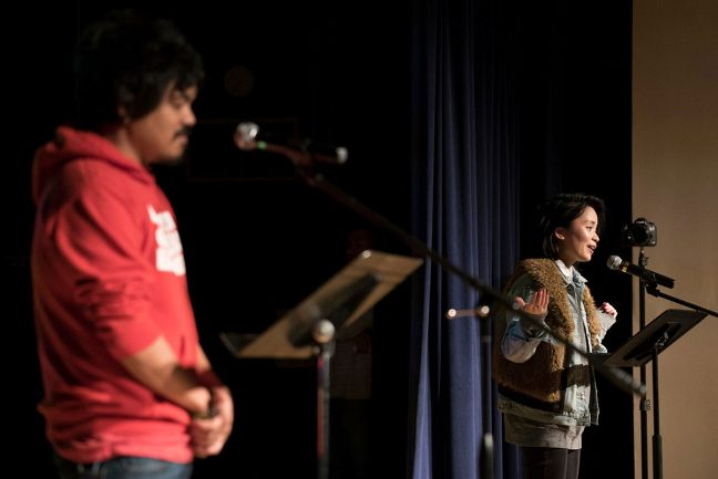 Two Filipino Americans stand on stage in front of microphones presenting Filipino American stories.