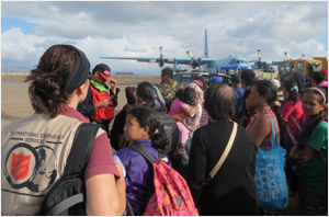 Damaris Frick with queues of people waiting to leave on emergency flights from Tacloban Airport