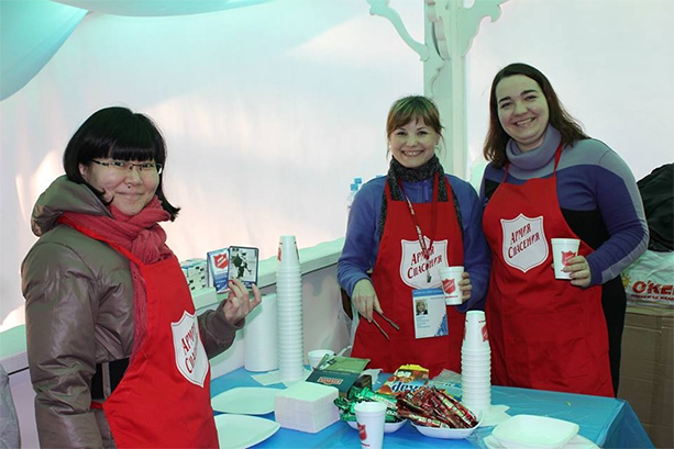 Team members Natasha, Julia and Anastasia serving drinks and offering literature