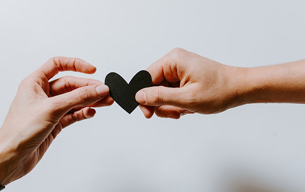 Two hands holding a heart shape