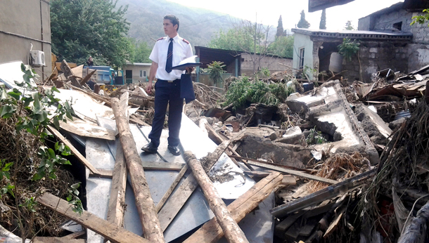 Captain David Kotrikadze (Finance and Property Officer, Georgia Region) looks at damaged property in Tbilisi