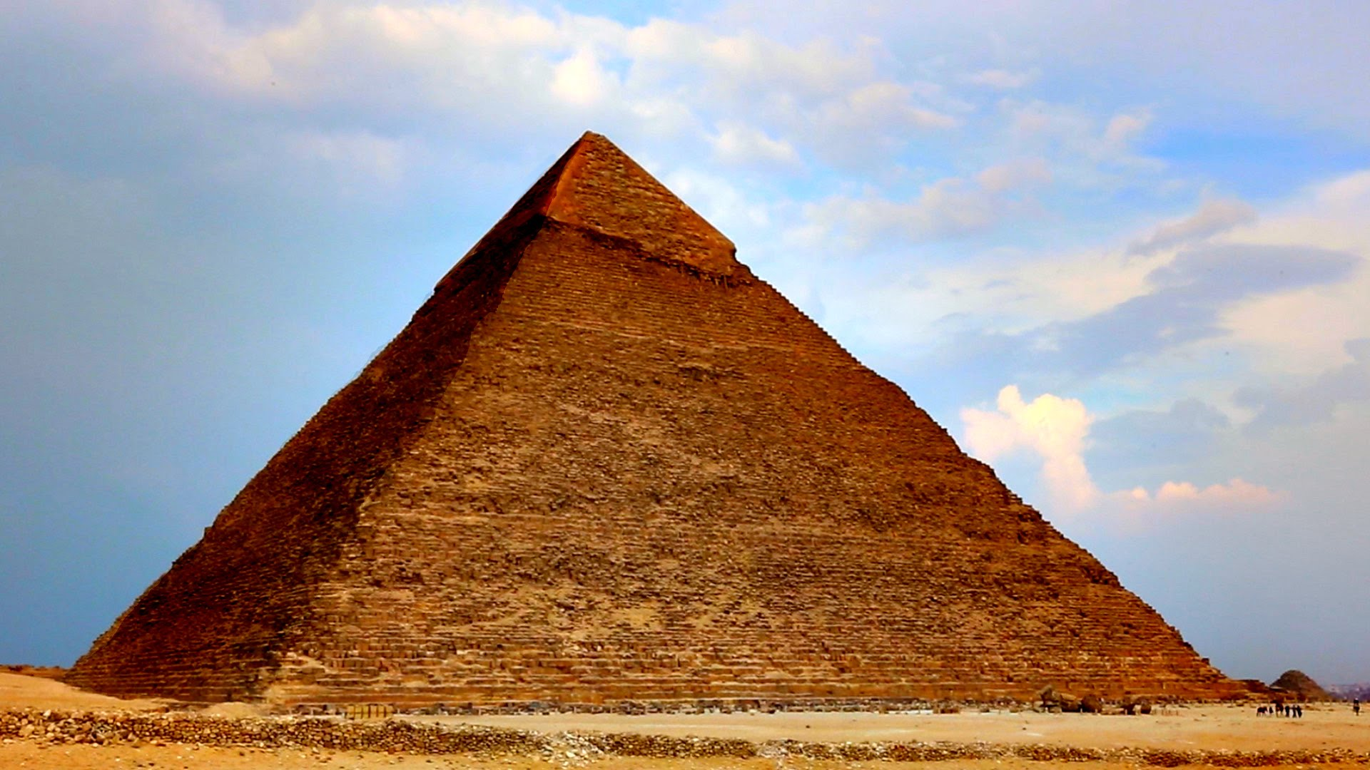 pirâmide com algumas pessoas no canto direito inferior, e no fundo o céu azul com algumas nuvens e manchas rosas