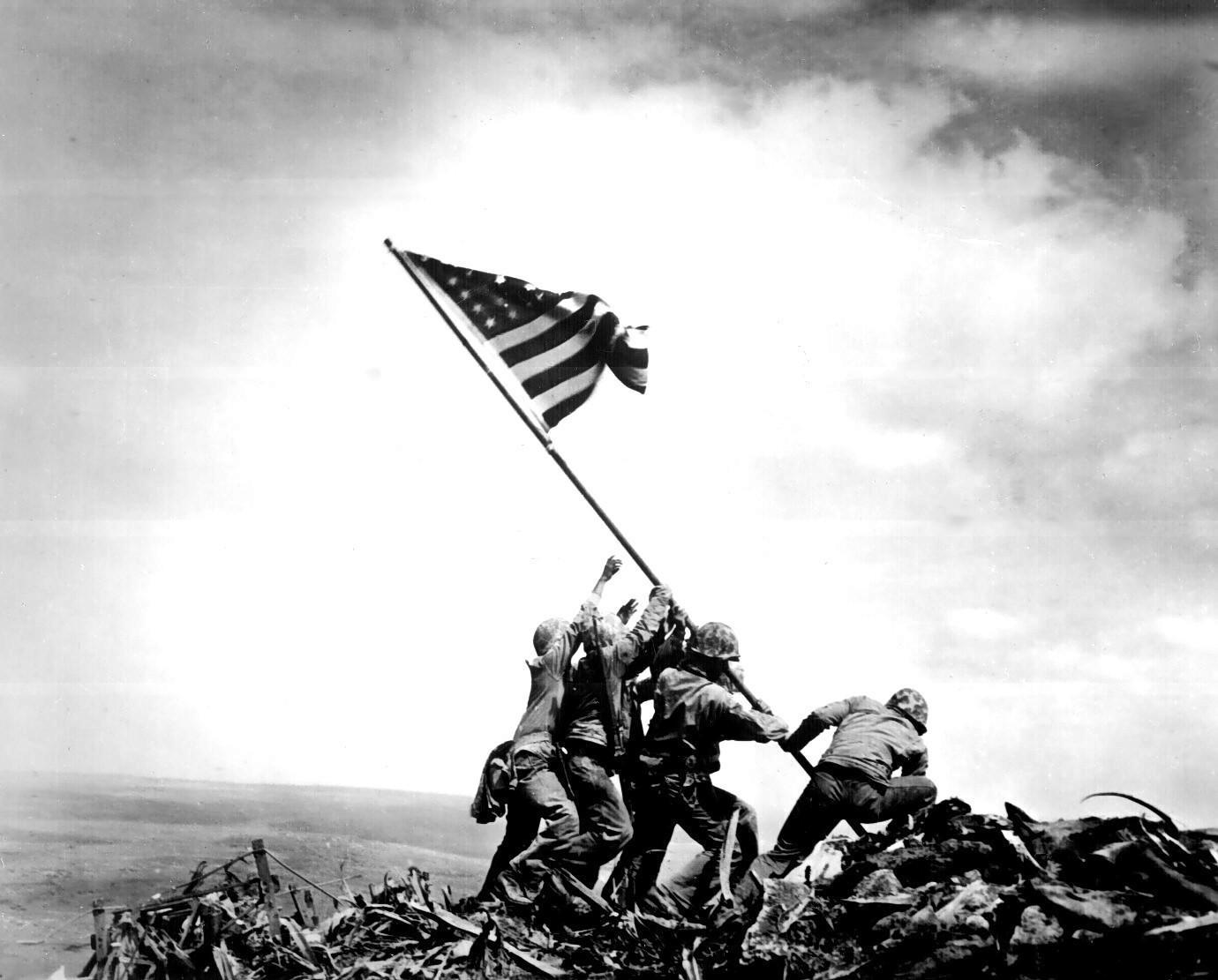 soldados andando sobre uma pilha de destroços, carregando uma haste com a bandeira americana