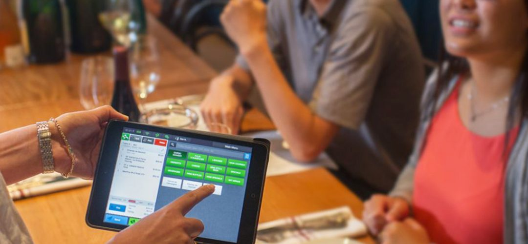 Server taking table side order with a mobile POS Solution by CAKE from Sysco.