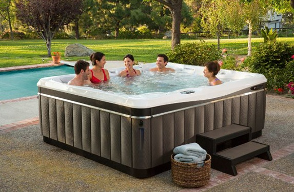 a group of friends relaxes and soaks in a beautiful yard with a lawn enjoying a utopia cantabria hot tub