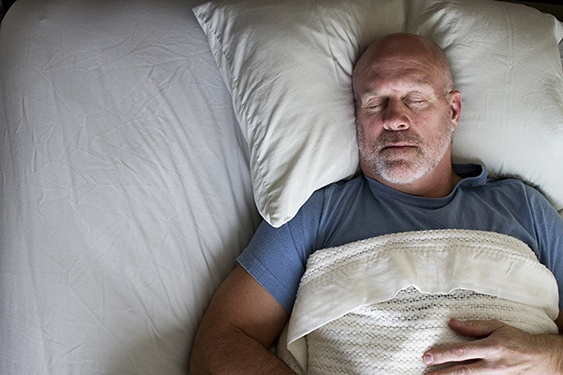 a man sleeps soundly in his bed by avoiding electronics before bed time