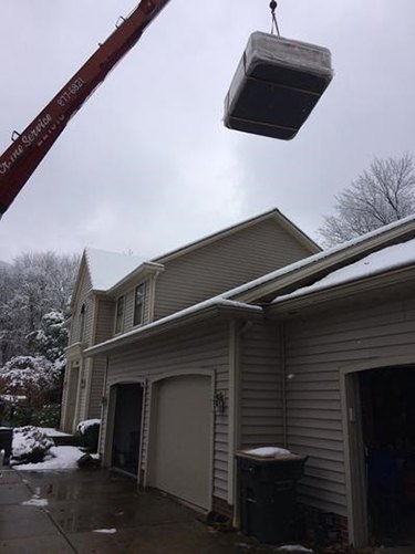 a hot tub is lifted by crane over a house to be placed in the backyard