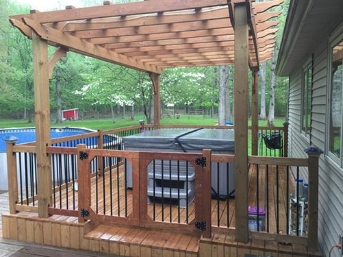 a Caldera hot tub sits in a backyard underneath a pergola with a safety fence
