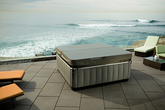 A Utopia Spa perched on a cliffside patio with the ocean in the background demonstrates the energy efficiency of the best quality hot tub covers