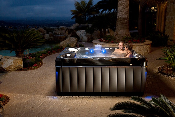 night time patio scene couple enjoys the premium luxury hot tub