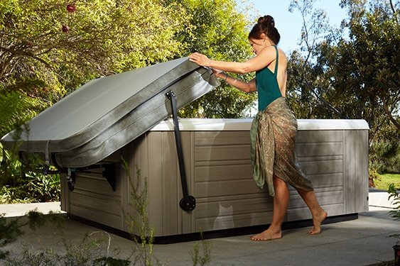 A lady demonstrates one person operation of a hot tub cover lifter on her back patio