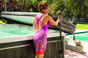 a woman operates her hot tub cover lifter proving that opening your spa with a hot tub cover lifter is a one person job