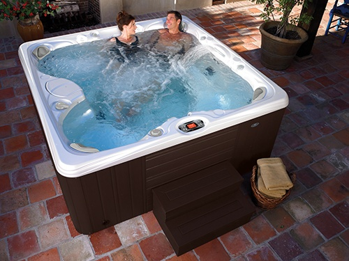 a couple relaxes in a paradise salina jacuzzi on a beautifully designed backyard patio