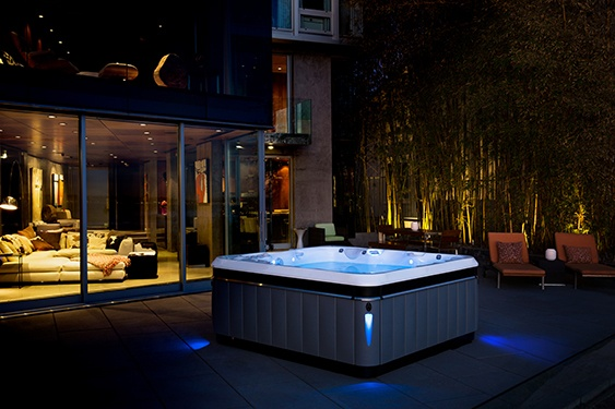 a luxury designer Utopia Tahitian hot tub sits center stage and exposed on a patio