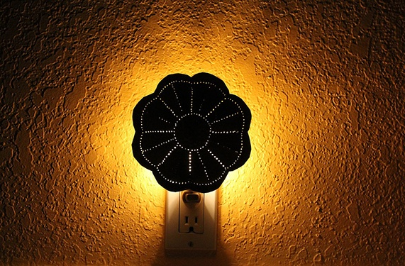 a nightlight on a wall shows that dark room promotes improved sleep quality