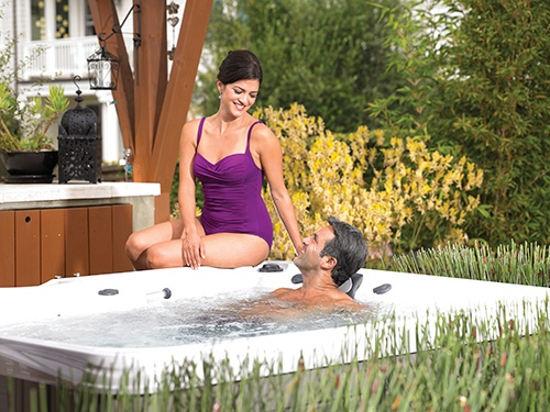 a woman discusses the best hot tub water care system with her husband